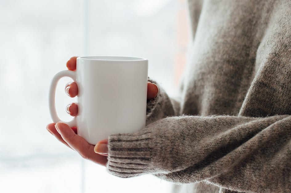 Close up of women's hands holding white mug with blank copy spac